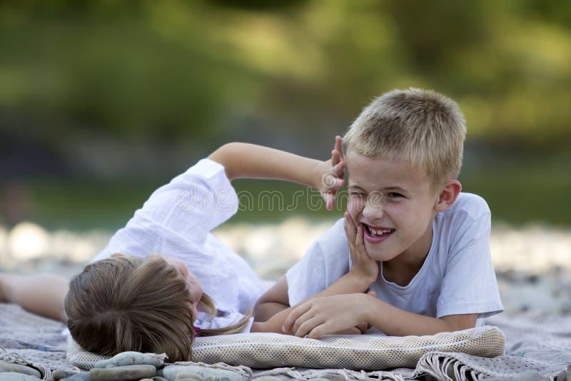 Två unga lyckliga gulliga blonda skratta barn, pojke och flicka, brot arkivfoto