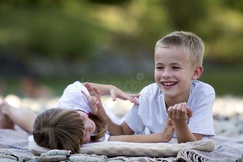 Två unga lyckliga gulliga blonda skratta barn, pojke och flicka, brot royaltyfri fotografi
