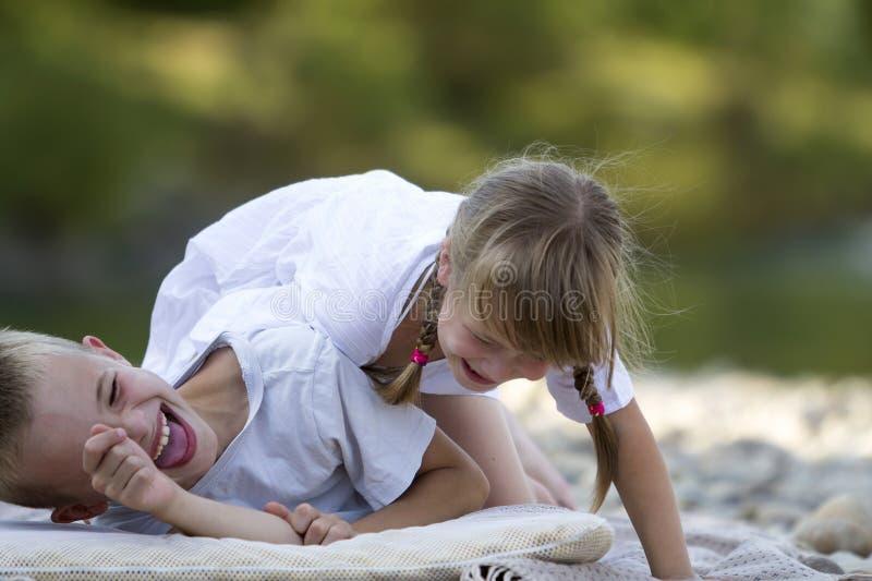 Två unga lyckliga gulliga blonda skratta barn, pojke och flicka, brot royaltyfri bild