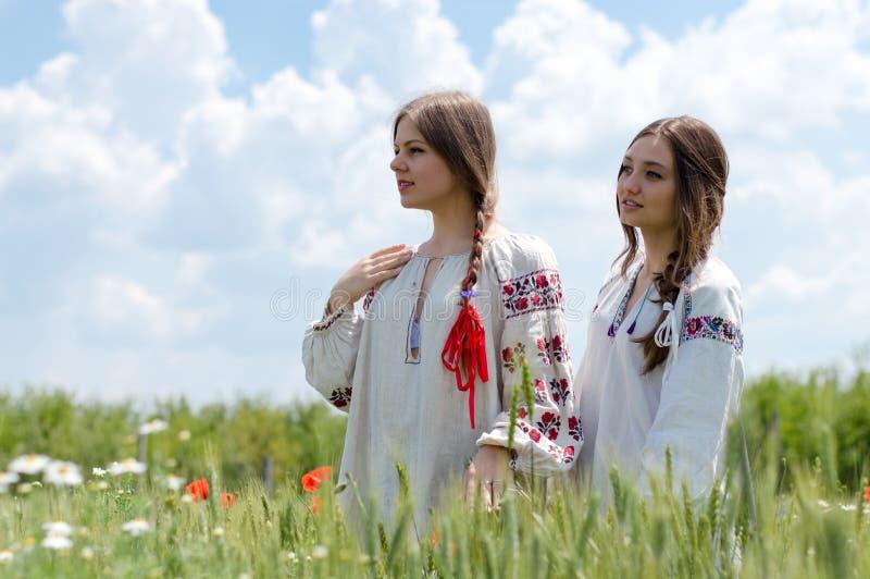 Två unga lyckliga kvinnor i traditionell ukrainsk klänning i vetefält royaltyfri bild