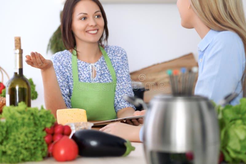 Två unga lyckliga kvinnor lagar mat i köket Vänner har gyckel, medan preapering sunt och smakligt mål royaltyfria bilder