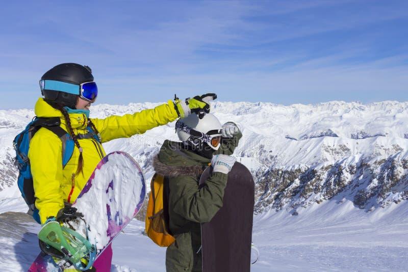 Två unga lyckliga vänner som snowboarders har gyckel skidar på, lutningen med snowboards i solig dag royaltyfri bild