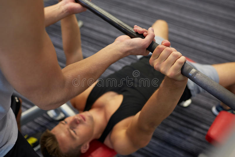 Två unga män med skivstången som böjer muskler i idrottshall royaltyfri bild