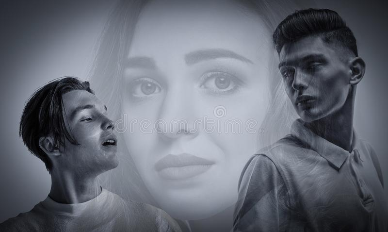 Två unga män och skugga av kvinna i grå bakgrund arkivfoto