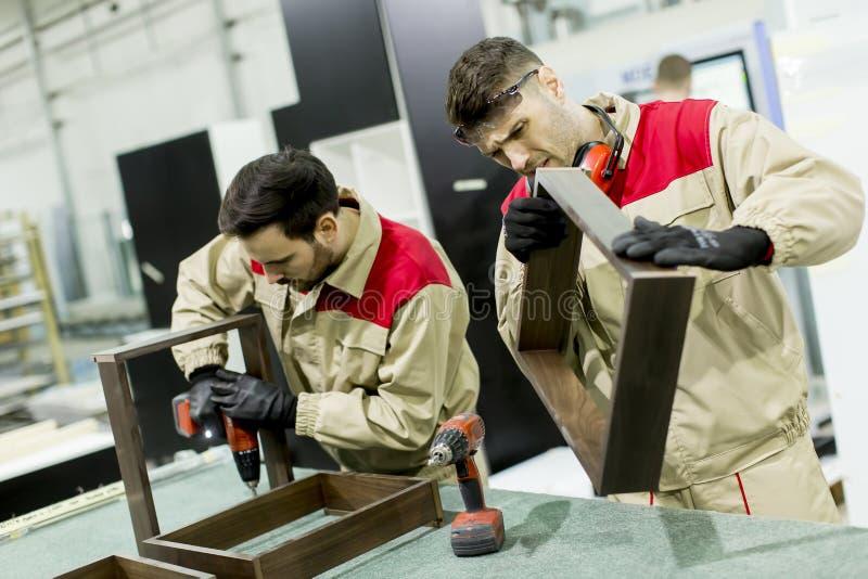 Två unga män som arbetar i en fabrik arkivfoton