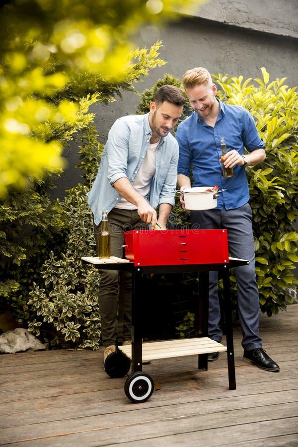 Två unga män som förbereder grillfesten i borggården royaltyfria bilder