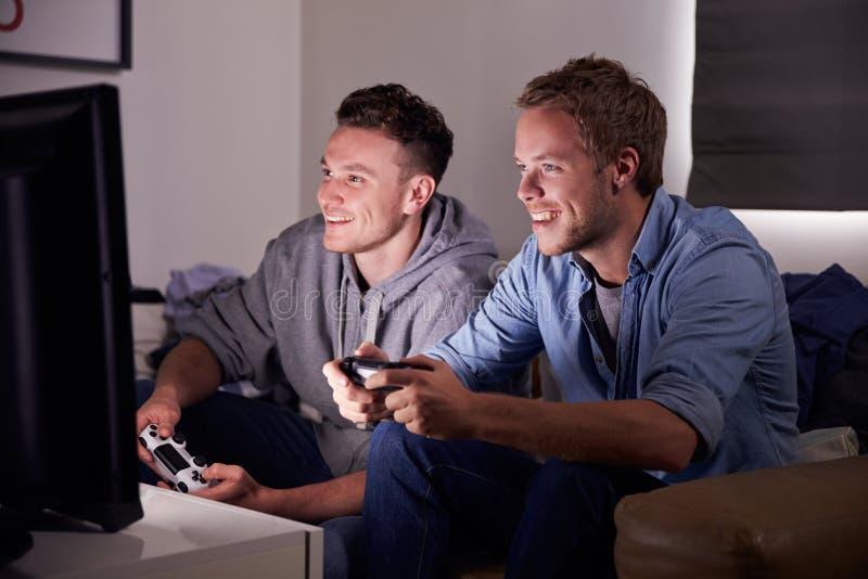 Två unga män som hemma spelar videospelet arkivfoton