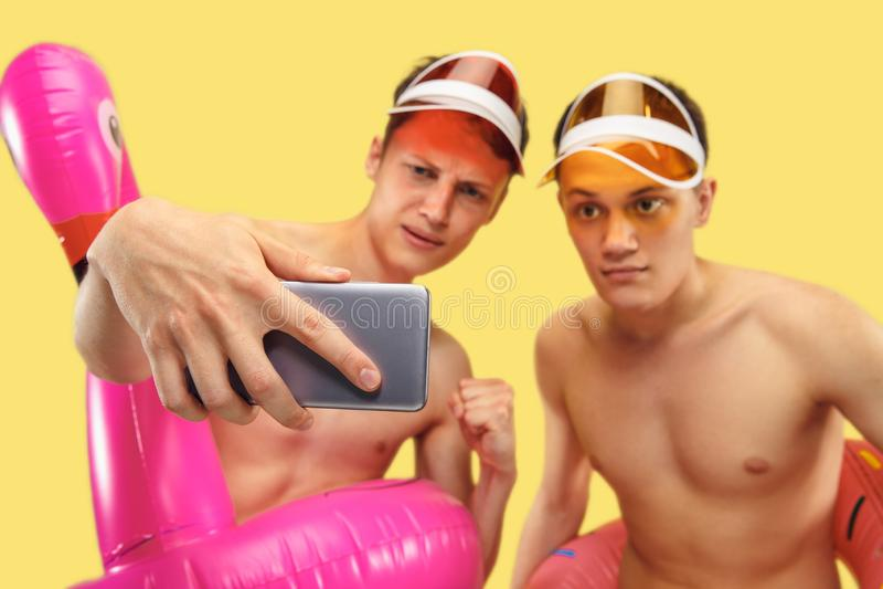 Två unga män som isoleras på gul studiobakgrund royaltyfria foton