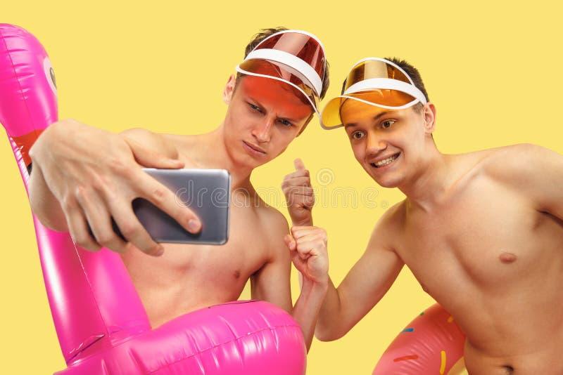 Två unga män som isoleras på gul studiobakgrund arkivbilder