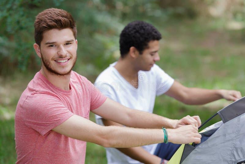 Två unga män som kastar upp deras tält royaltyfri fotografi