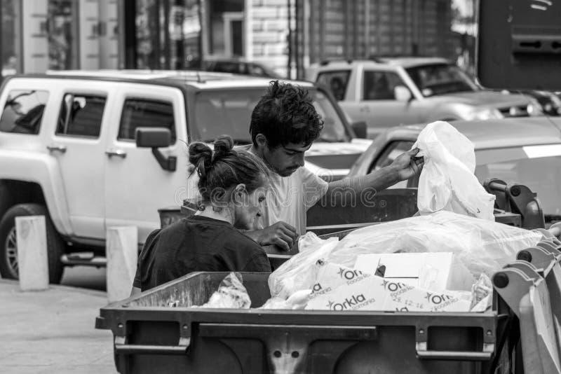 Två unga män som söker i ett avfallfack nära det Bucharest universitetet royaltyfri bild