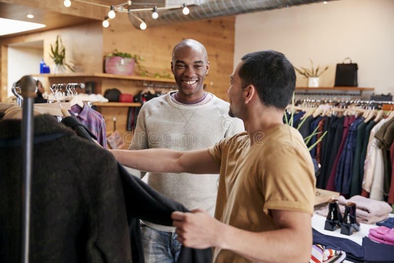 Två unga män som shoppar för kläder i kläder, shoppar arkivbild