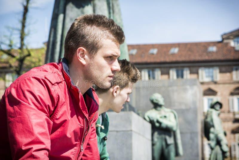 Två unga män som sitter på den låga väggen i stads- inställning arkivfoton