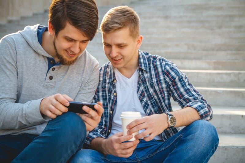 Två unga män som sitter på momenten arkivbilder