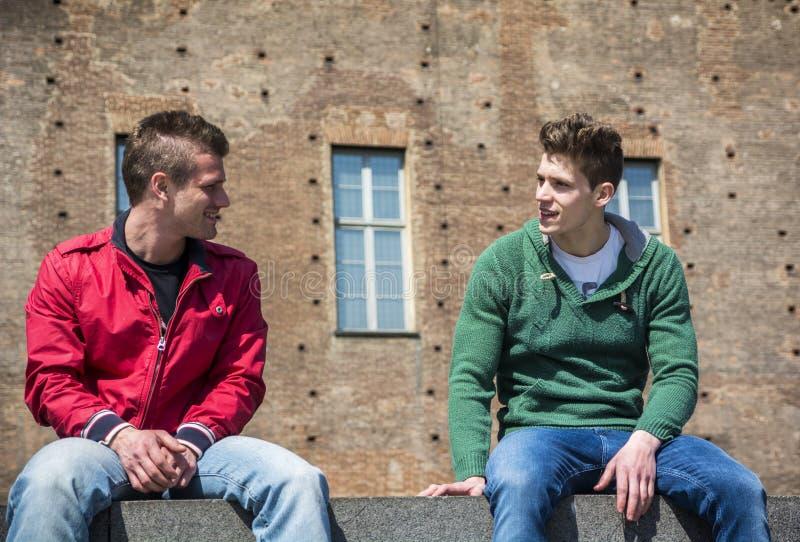 Två unga män som talar, medan sitta på trottoarkant royaltyfri foto