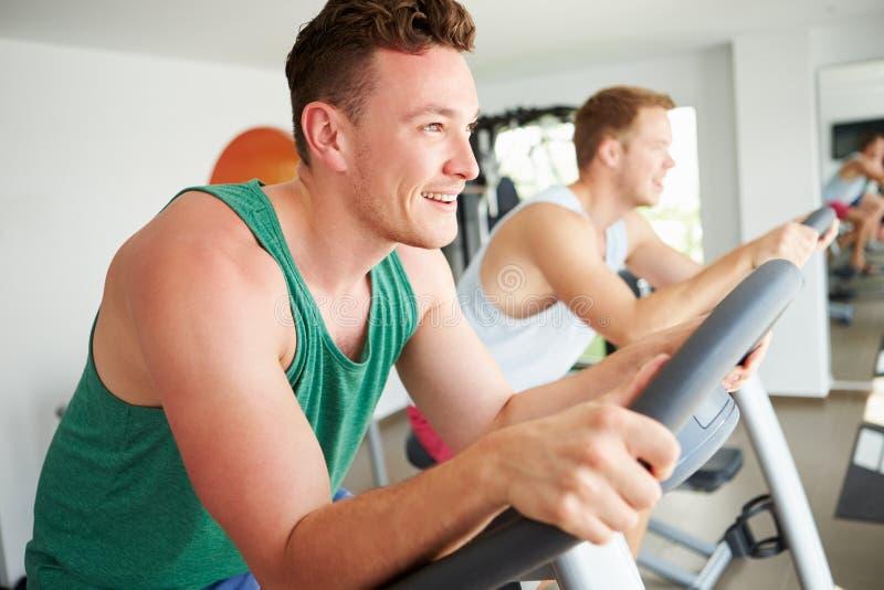 Två unga män som utbildar i idrottshall på att cykla maskiner tillsammans fotografering för bildbyråer