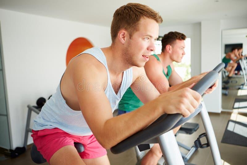 Två unga män som utbildar i idrottshall på att cykla maskiner tillsammans arkivfoton