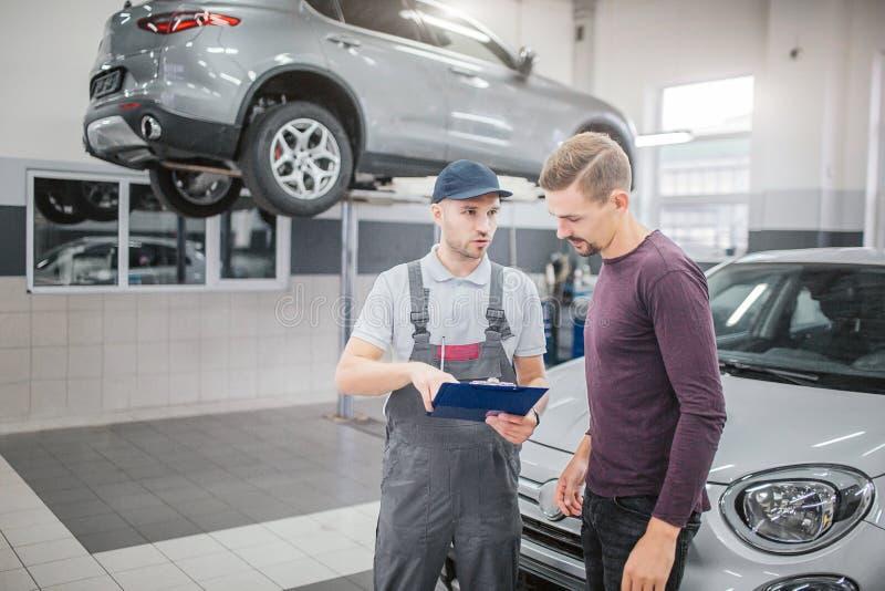 Två unga män står i garage på bilen och samtal Grabb i enhetliga hålldokument och punkt på dem Han ser uppsökt arkivfoto