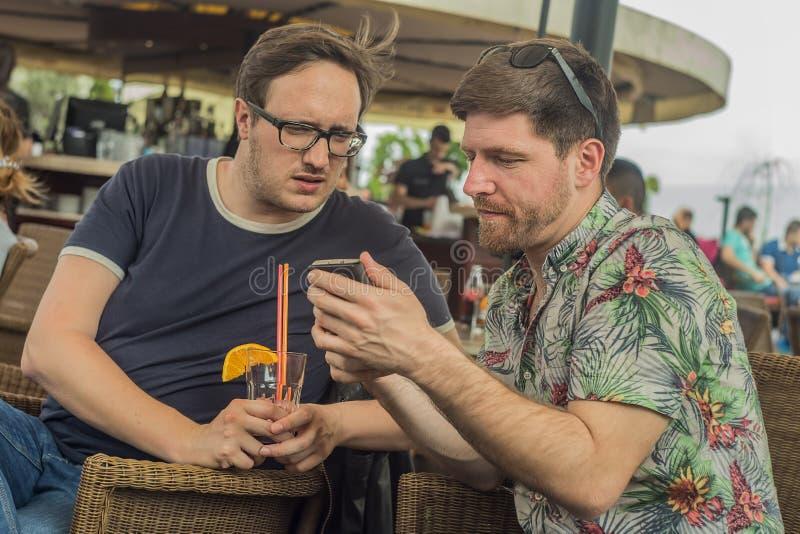 Två unga manliga vänner som har gyckel, dricker coctailar och pratar med vänner på terrasskafét i stad arkivfoto