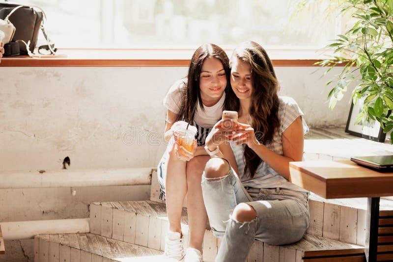 Två unga nätta flickor med långt mörkt hår, bärande tillfällig dräkt, sitter på trappan och ser telefonen i en slags tvåsittssoff arkivbild