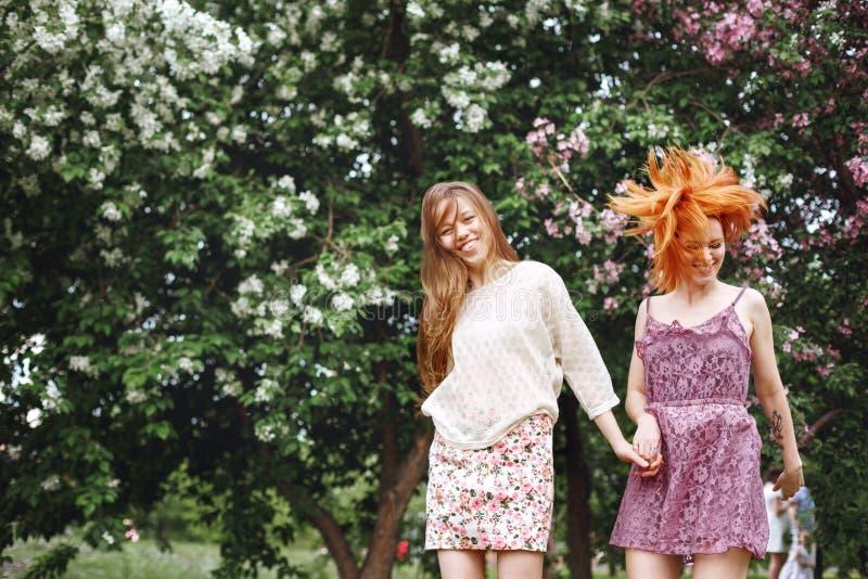 Två unga nätta flickor som har roligt utomhus royaltyfri bild