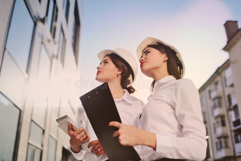 Två unga nätta industriella teknikerer för affärskvinnor i konstruktionshjälmar med en minnestavla i händer på en glass byggnad arkivfoto