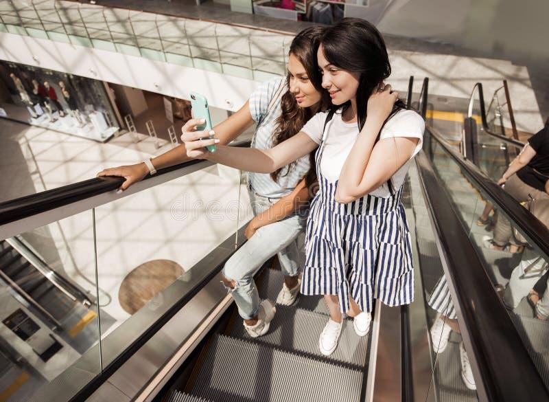 Två unga nätta slanka flickor, bärande tillfällig stil, står bredvid de på rulltrappan i en ny galleria fotografering för bildbyråer