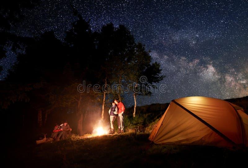 Två unga par på lägereld under ljus stjärnklar himmel nära tältet på bakgrund av träd arkivbilder