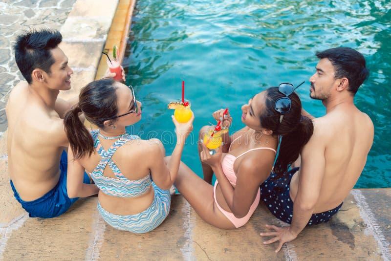 Två unga par som dricker coctailar, medan koppla av tillsammans på pölen royaltyfria bilder