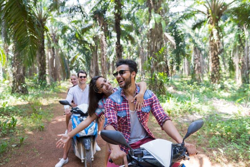 Två unga par som kör sparkcykelcykeln i tropisk tur för Forest Young Group Of People danandeväg i Wood palmträd arkivfoto