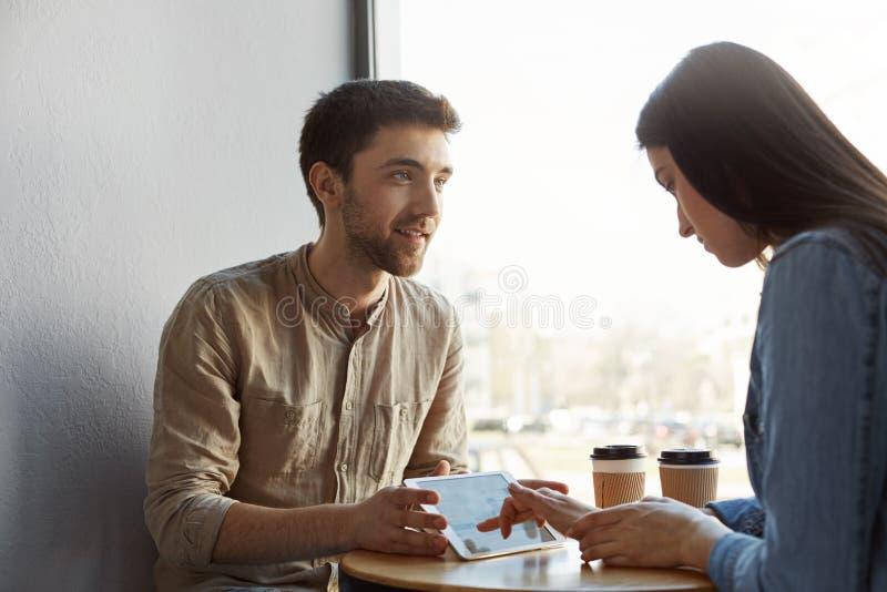 Två unga pesrpective entreprenörer på möte som dricker kaffe, talar om det framtida start-up projektet och ser throug arkivfoto