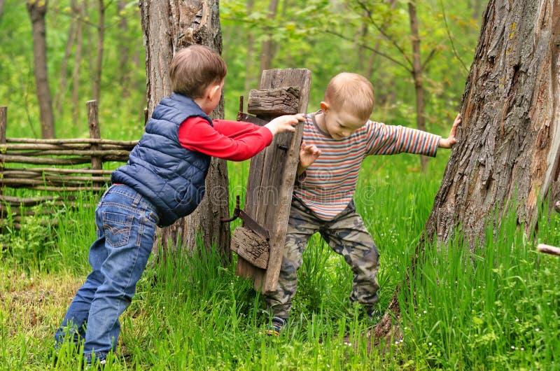 Två unga pojkar som slåss över en lantlig gammal port royaltyfri foto