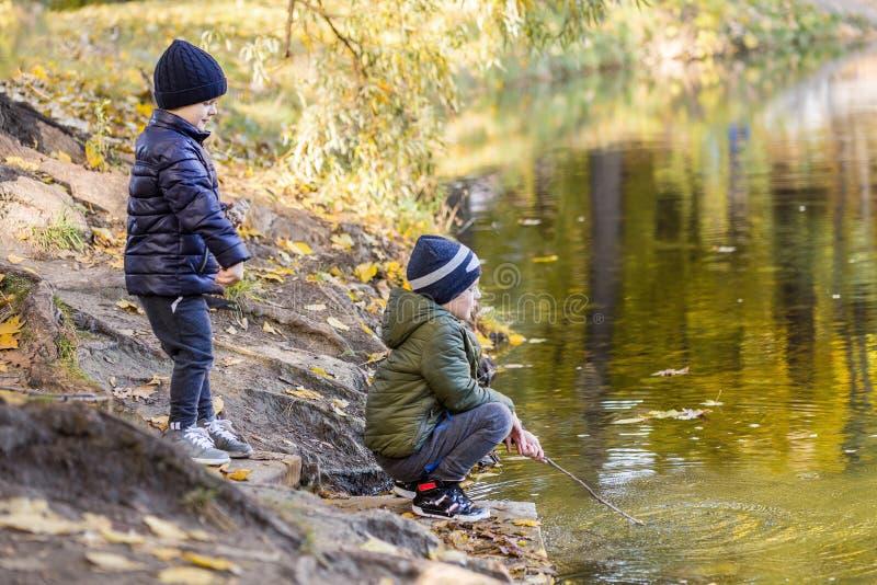 Två unga pojkar som spelar fiske med pinnar nära dammet i nedgång, parkerar Små bröder som har den roliga near sjön eller floden  royaltyfri fotografi
