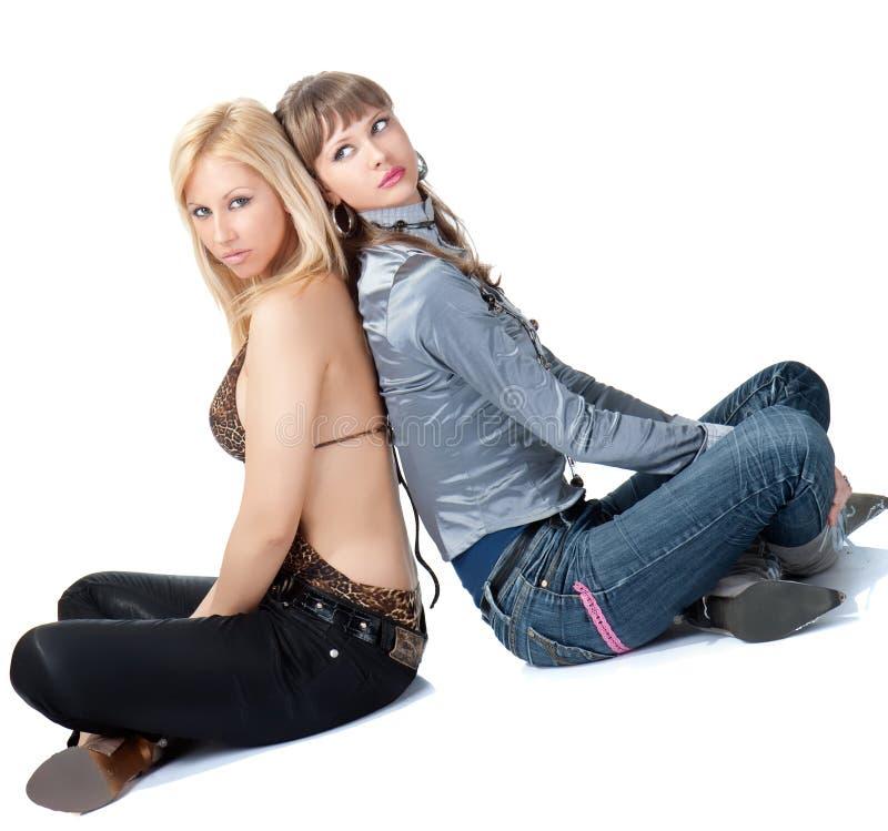 Två unga prety kvinnor sitter på golv royaltyfri foto