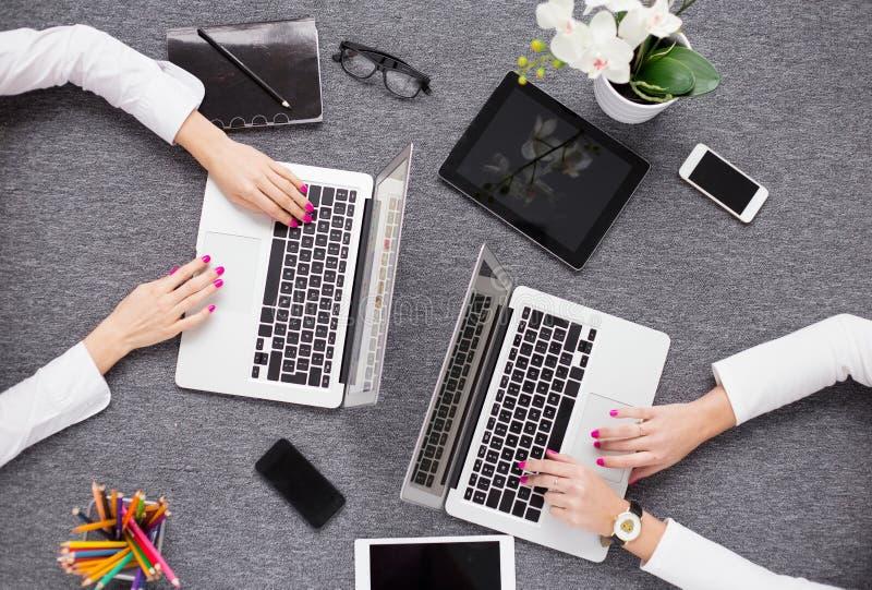 Två unga professionell som arbetar med datoren, sikt från över royaltyfria bilder