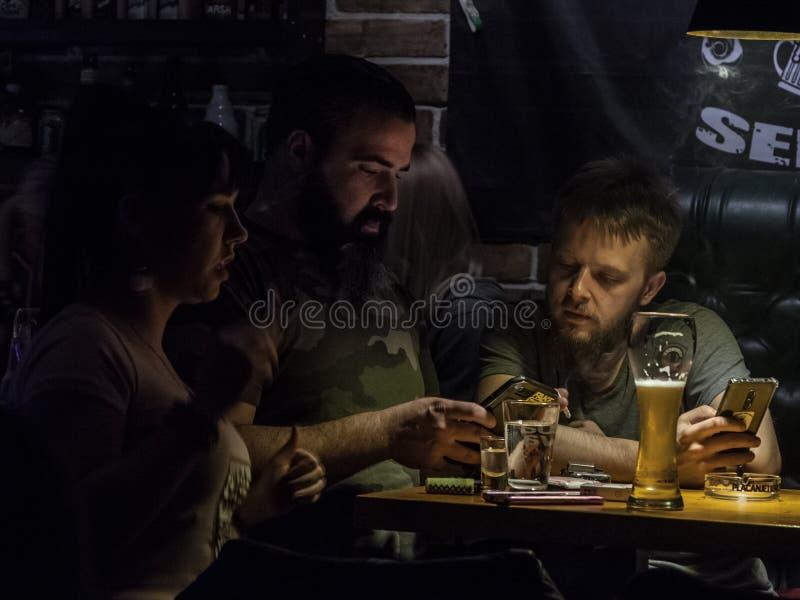 Två unga skäggiga män, vita caucasian män som dricker öl i en barstång, medan se internet på smartphones arkivfoto
