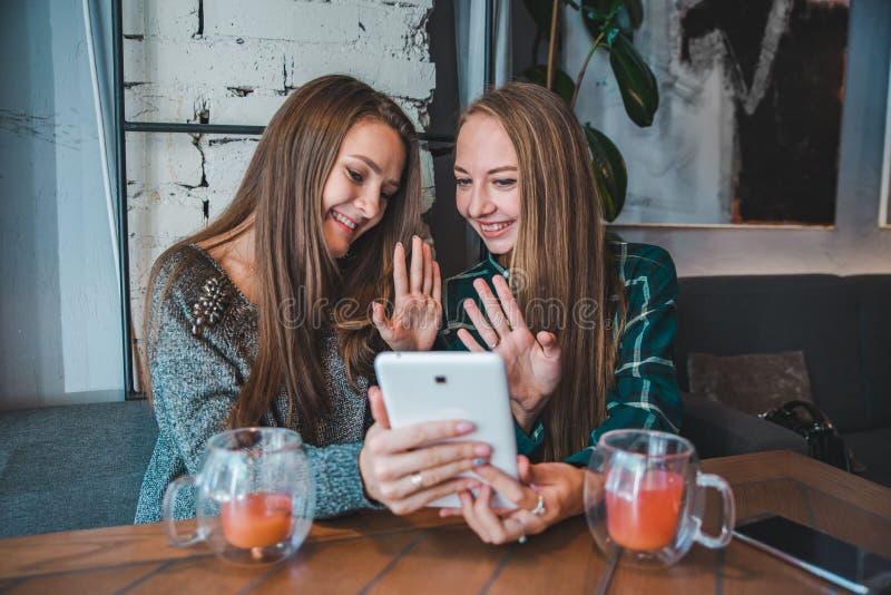 Två unga skönhetkvinnor som talar vid video pratstund genom att använda minnestavlan sitta i kafét som dricker te arkivfoton