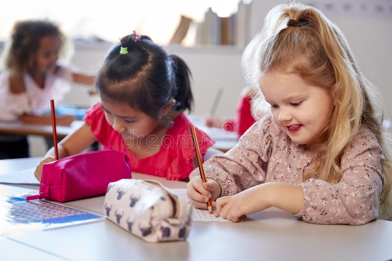 Två unga skolflickor som sitter på ett skrivbord i ett klassrum för begynnande skola som arbetar, slut upp arkivbild