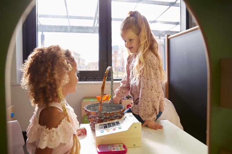 Två unga skolflickor som spelar för att shoppa i en lekstuga på en begynnande skola som är bakbelyst royaltyfri foto