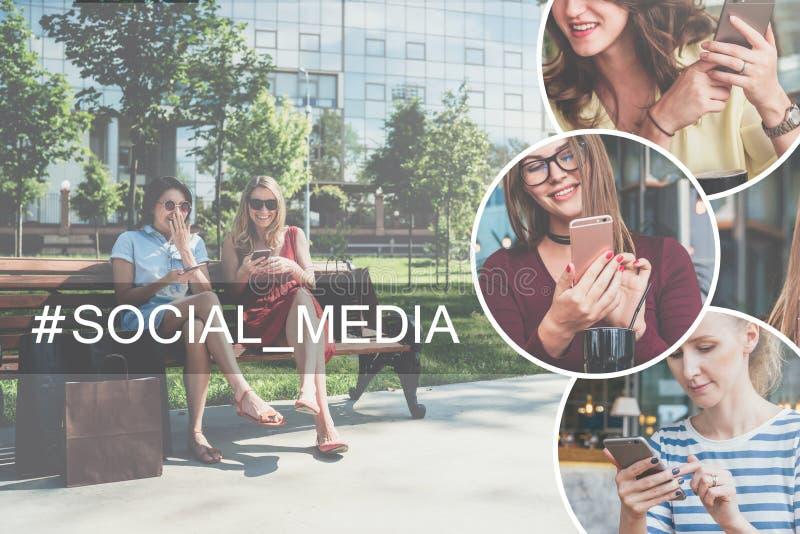 Två unga skratta kvinnor i klänningar som sitter på en parkerabänk, vilar, når att ha shoppat och de har använt deras smartphones royaltyfri foto