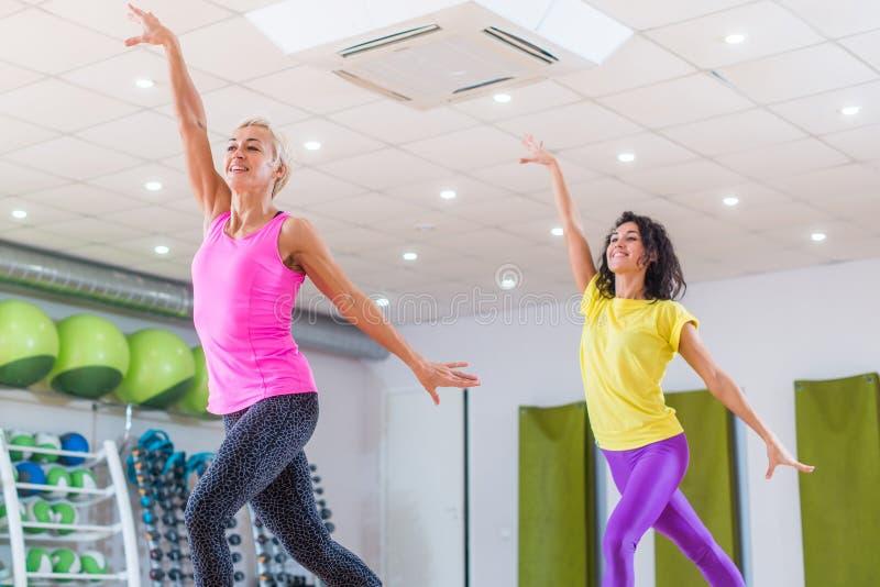 Två unga sportiga kvinnor som övar i studio, dans, att göra är cardio, arbete på jämvikt och koordination för kondition som royaltyfria bilder