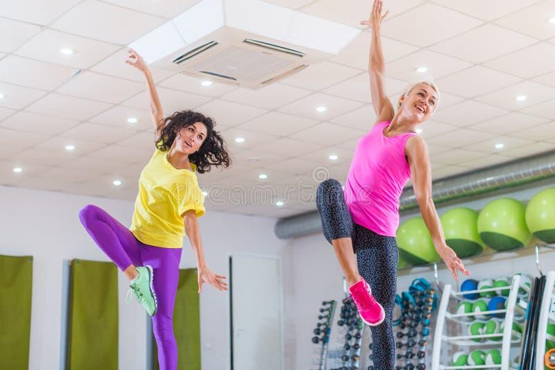 Två unga sportiga kvinnor som övar i studio, dans, att göra är cardio, arbete på jämvikt och koordination för kondition som arkivfoto