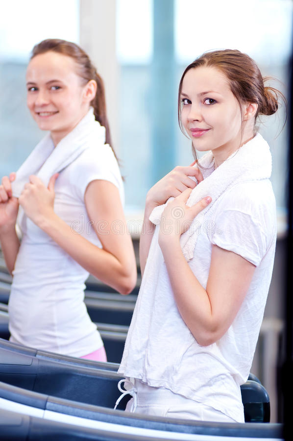 Två unga sportiga kvinnor som körs på maskinen royaltyfria bilder