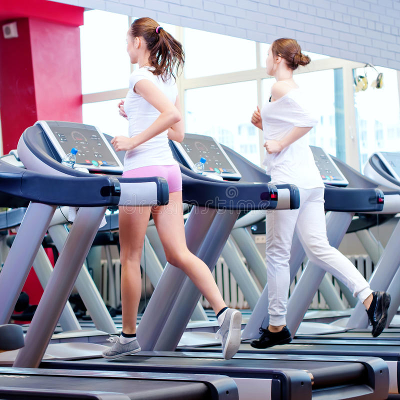 Två unga sportiga kvinnor som körs på maskinen royaltyfri bild