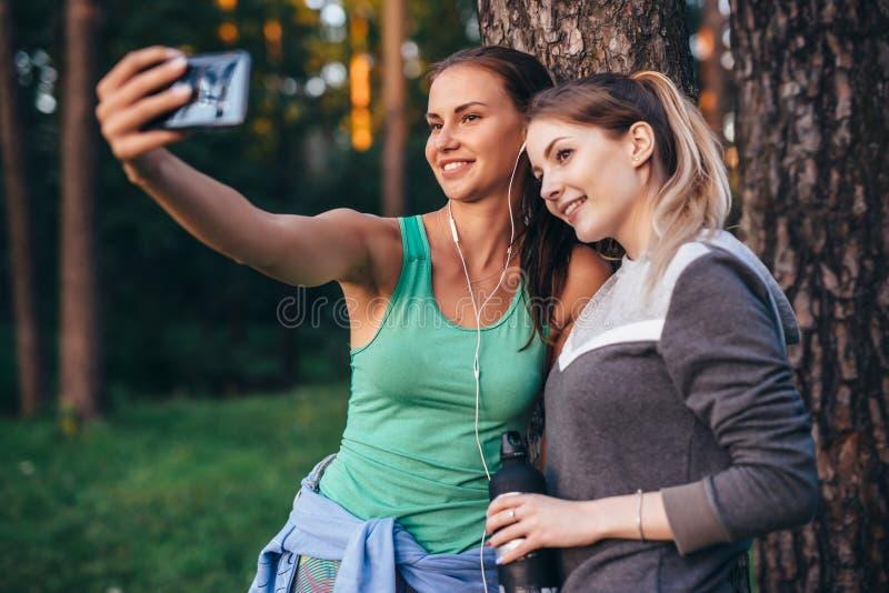 Två unga sportive flickvänner som bär sportswearbenägenhet mot trädet som tar selfie med smartphonen i skog royaltyfria foton