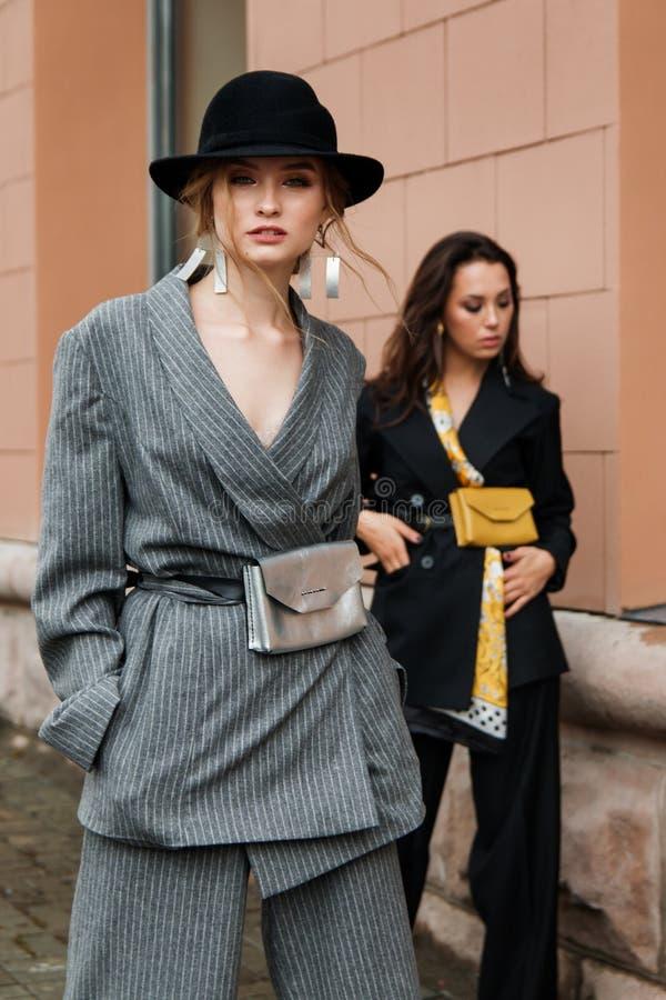 Två unga stilfulla härliga kvinnamodemodeller poserar i gatan, den bärande byxdressen, hatt och att ha handväskan på midjan royaltyfri bild