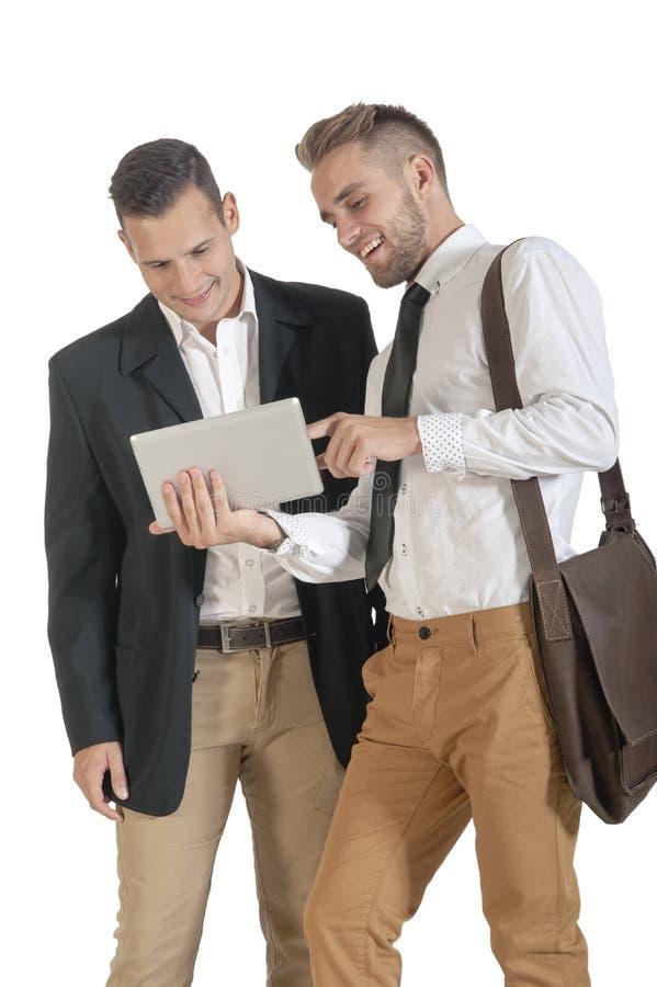 Två unga stiliga affärsmän som arbetar med den digitala minnestavlan arkivbild