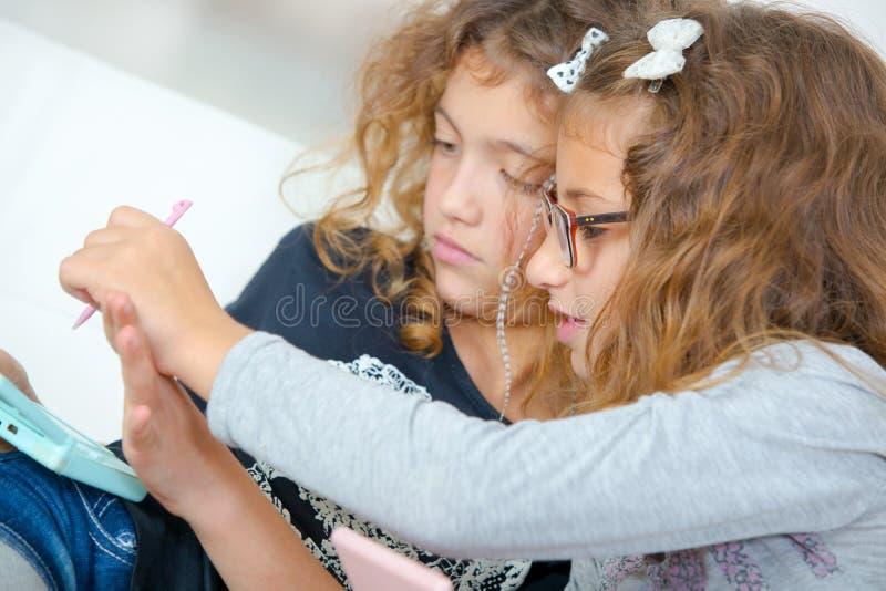 Två unga systrar som spelar videopp kulingar royaltyfri foto