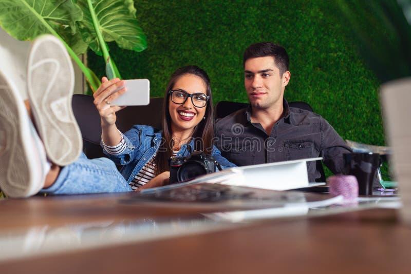 Två unga teknikerer som tar en selfie i kontoret arkivfoto