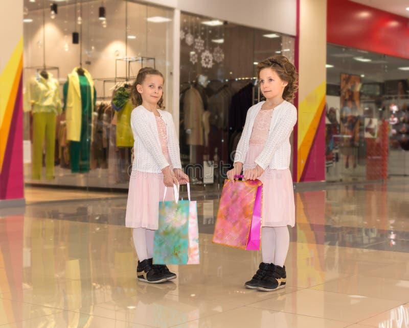 Två unga tvilling- systrar med shoppingpåsar som går på gallerian royaltyfri bild